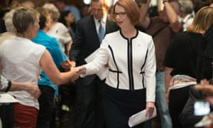 Australian Prime Minister Julia Gillard greets members of the audience as she arrives to the National Apology for Forced Adoptions ceremony at Parliament House in Canberra.