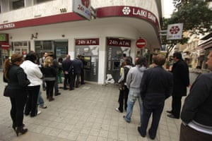 Cypriots and foreigners wait in line to withdraw money from an ATM of a Laiki (Popular) Bank branch in the old city of the capital, Nicosia, on March 21, 2013.