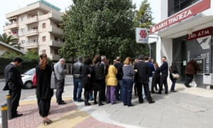 People wait in line to withdraw money from an ATM at a closed Bank of Laiki branch, in Nicosia, Cyprus, 21 March 2013.