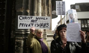 Demonstrators protest against government cuts to the NHS as guests arrive at the gates of Canterbury Cathedral.