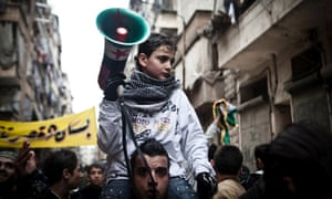 A boy carries a megaphone during a protest in Aleppo, Syria, where young people and children sang songs against President Bashar al-Assad and his regime.