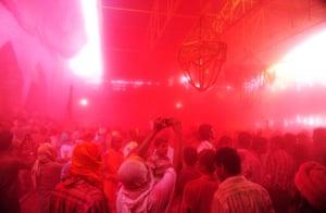 Hindus throw coloured powder at the Radha Rani temple during the Lathmar Holi festival in Barsana, India.