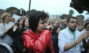 A protester cries during a rally by employees of Cyprus Popular Bank outside the parliament in Nicosia.