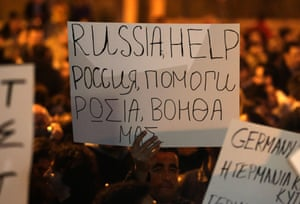 A Cypriot holds a placard during a protest outside the Parliament on March 21, 2013 in Nicosia.