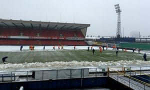 Ground staff help clear snow away from Windsor Park on 22 March 2013.
