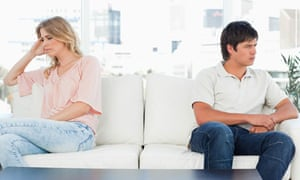 Man and woman sitting at opposite ends of couch