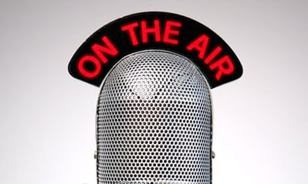 Retro microphone with an On the Air illuminated sign on a desk vignetted background