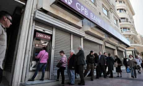 Cypriots queue at a cash machine