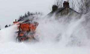 A snow plough clears the A6 road near Buxton