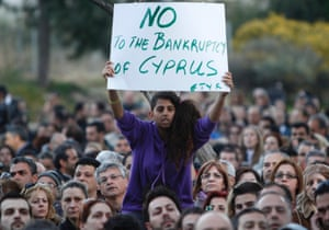 Bank employees afraid of losing their jobs, a young woman holding a poster which reads 'No to the bankruptcy of Cyprus', protest outside the Ministry of Finance in Nicosia, Cyprus, 23 March 2013.