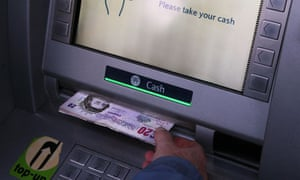 A woman uses a barclays bank cash machine