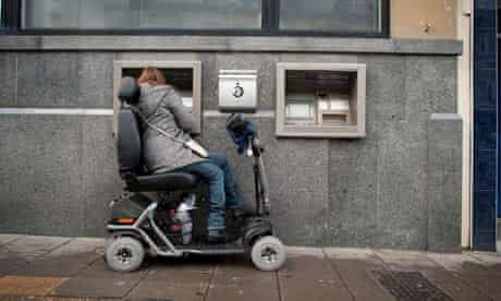 A woman in a powered wheelchair uses a cash machine, UK