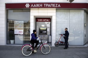 A woman rides her bike past a Laiki (Popular) Bank branch on March 25, 2013 in Nicosia.