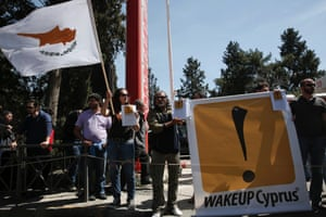 Anti-bailout protesters hold a banner and a Cypriot flag during a student parade marking Greece's Independence Day in Nicosia March 25, 2013