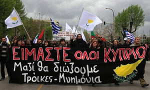"Protesters hold a banner that reads "" We are all Cypriots Together we will send away Troika and Memorandums"" as they protest against financial measures imposed to Cyprus during a parade to commemorate the independence day at the northern Greek city of Thessaloniki on Monday March 25, 2013."