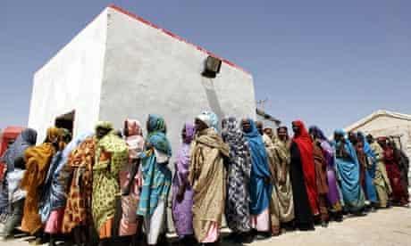 Displaced Sudanese women wait in line fo