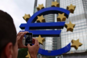 A man takes a picture with a mobile phone of the euro sign at the European Central Bank (ECB) headquarters in Frankfurt July 11, 2012.