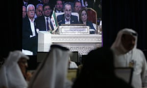 Moaz al-Khatib, head of the Syrian opposition delegation, appears on a screen as he addresses the opening of the Arab League summit in the Qatari capital Doha on March 26, 2013.
