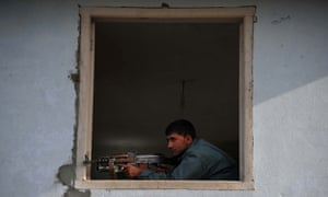 An Afghan policeman takes up a position at the site of a suicide attack on the police headquarters in Jalalabad