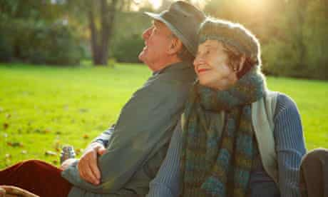 Senior couple sitting side by side in a park.