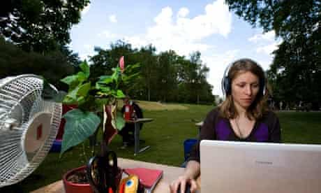 woman working at her desk in a green field