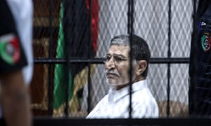 Former Libyan foreign intelligence chief Bouzid Dorda sits behind bars in the defendant's cage during a session of his trial in Tripoli, Libya. Dorda is facing charges of killing protesters during the 2011 uprising. He is denying all accusations against him.