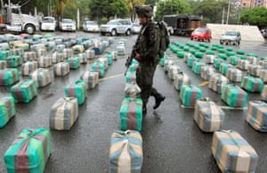 A police officers guards bulks of seized marijuana on display for a media presentation at police headquarter in Cali, Colombia. According to police the 7.7 tons of marijuana were seized from the rebels of the Revolutionary Armed Forces of Colombia, FARC, during a raid in a highway near Cali.