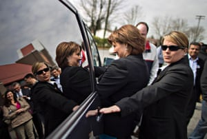 A bodyguard watches over British Columbia Premier Christy Clark (L) as she gets into her car after meeting supporters in Surrey, British Columbia, Canada. Clark visited supporters and candidates while preparing for a provincial election to be held May 14.