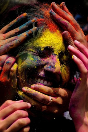 An Indian girl is smeared in coloured powder as she celebrates Holi in Bangalore, India. Holi is celebrated at the end of the winter season on the last full moon day of the lunar month Phalguna (February or March). The main day is celebrated by people throwing colored powder and colored water at each other.