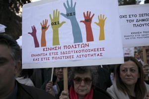 Demonstrators hold banners as they protest outside the European Union House in the Cypriot capital Nicosia on March 27, 2013.