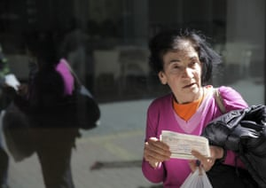 A woman holds cheques outside a closed Laiki bank branch in the old part of the Cypriot capital, Nicosia, on March 28, 2013, ahead of their reopening after an unprecedented 12-day lockdown.
