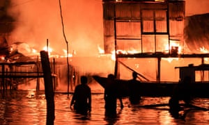 Locals watch their homes engulfed by flames as a fire destroys 400 wooden houses leaving 3,000 people homeless, Kota Kinabalu, Malaysia.