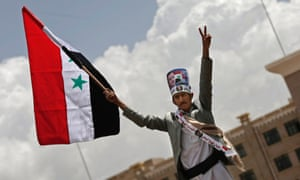 A Yemeni man holds the Syrian flag during a rally in support of President Bashar Assad in Sanaa, Yemen.