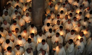 Roman Catholic clergymen hold candles as they circle the Anointing Stone during the Holy Thursday mass at the Church of the Holy Sepulchre in Jerusalem's old city ahead of Easter celebrations.