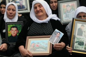 Family members of 34 Turkish Kurdish civilians, who were killed in Dec. 2011 in a botched raid on the Turkey-Iraq border by Turkish military jets, hold their pictures as they stage a protest outside Turkey's parliament in Ankara.
