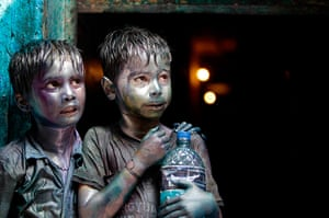 Holi festival: Hindu children smeared in colours stand at a doorway in Dhaka, Bangladesh