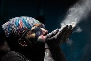 Holi festival: A Hindu man blows coloured powder during Holi festival celebrations