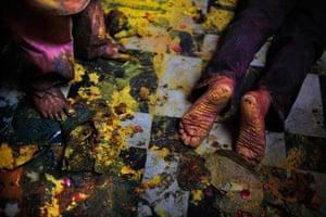 Holi festival: A Hindu devotee kneels down for prayers amid colors thrown