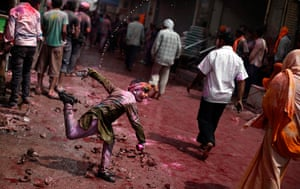 Holi festival: An Indian boy throws colored water on passers-by in Vrindavan