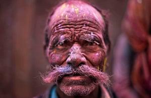 Holi festival: A Hindu devotee, face smeared with coloured powder,  Banke Bihari temple