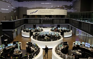 Traders are pictured at their desks in front of the DAX board at the Frankfurt stock exchange March 28, 2013.