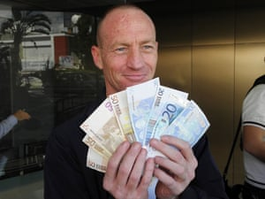 A man shows the money he got from Laiki Bank branch in Limassol, Cyprus 28 March 2013.