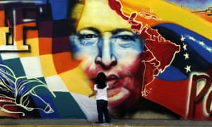 A child stands in front of a graffitti at the Mountain Barracks where the remains of late Venezuelan President Hugo Chavez are interned in Caracas.