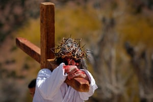 24 hours in pictures: Chimayo, New Mexico: A man playing the role of Jesus carries a cross during