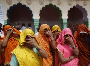 """24 hours in pictures: Mathura, India: Women cover their faces during """"huranga"""" at Dauji temple a"""