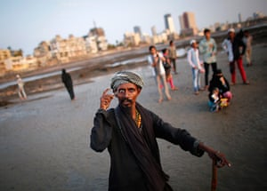 24 hours in pictures: Mumbai, India: A beggar holds his eye open with a knife as he asks for alms