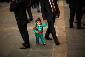 24 hours in pictures: Malaga, Spain: Child dressed up as a Spanish legionnaire, walks with her gr