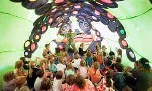 Children listen to a story inside an inflatable frog in the nylon zoo area