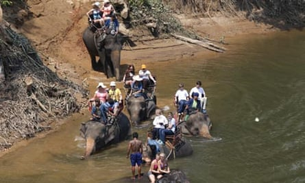 Tourists ride elephants in a river in Kanchanburi, Thailand