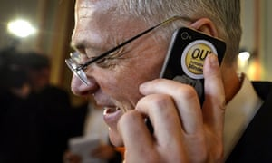 Thomas Minder uses a mobile phone bearing a 'yes' sticker while waiting for the referendum result